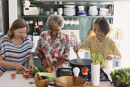 active senior women friends cooking in