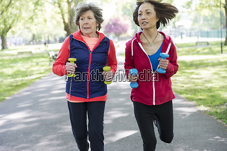 active senior women friends jogging with