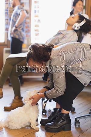 creative businesswoman petting cute dog in