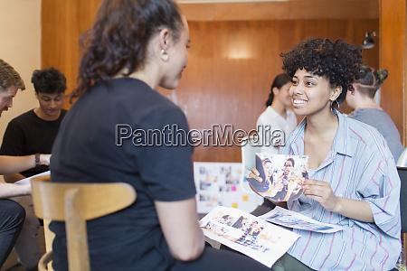 smiling creative female designers discussing photograph