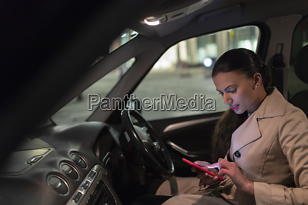 businesswoman with smart phone in car
