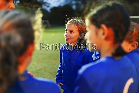 attentive girls soccer team listening to