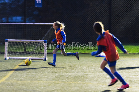 girls running playing soccer on field