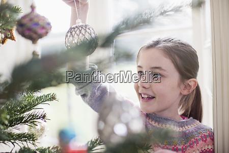 girl decorating hanging ornament on christmas