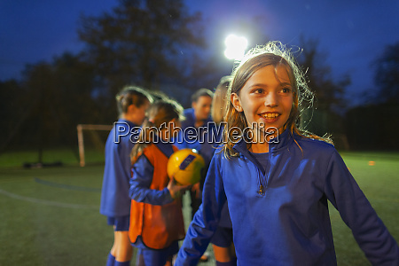 smiling girl playing soccer on field