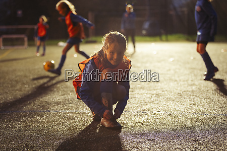portrait smiling girl soccer player tying