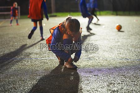 girl soccer player tying shoe on