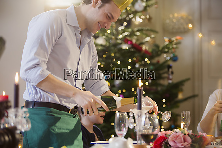 smiling man pouring champagne at candlelight