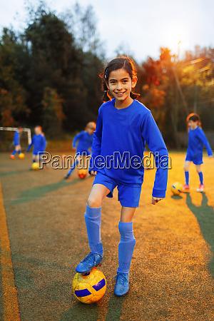 portrait confident girl practicing soccer on
