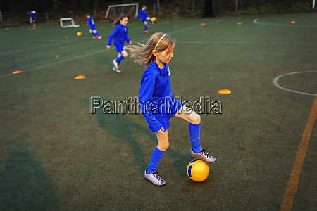 girl practicing soccer drill on field