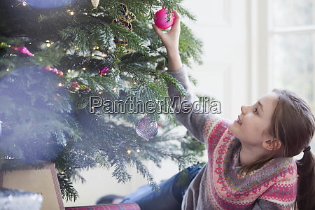curious girl touching ornament on christmas