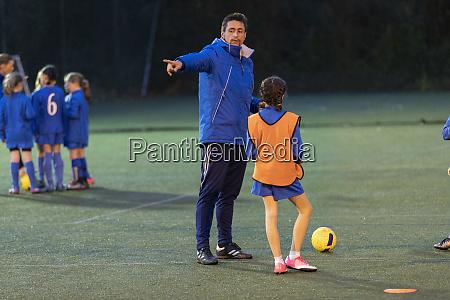 soccer coach guiding girl soccer players