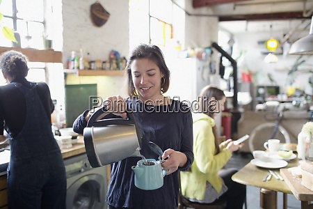 young woman pouring hot water into
