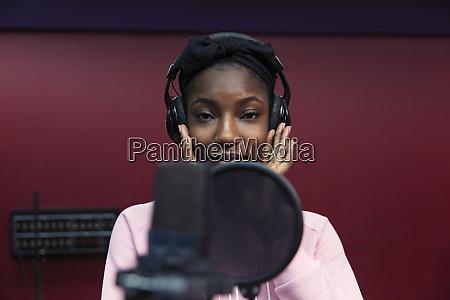 portrait confident teenage girl musician recording