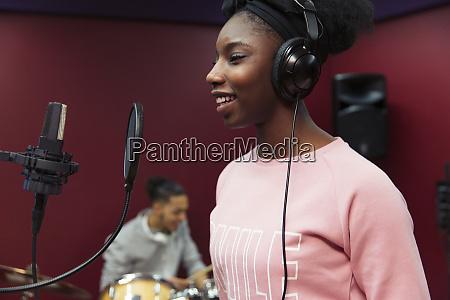 smiling teenage girl musician recording music