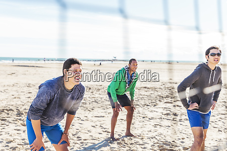 men playing beach volleyball on sunny
