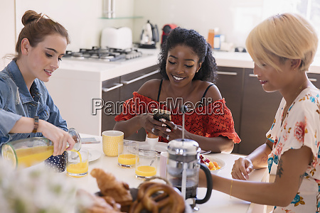 young women friends enjoying breakfast at