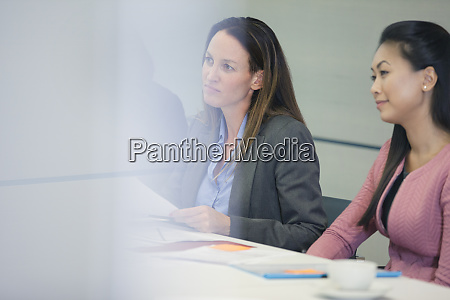 attentive businesswoman listening in conference room