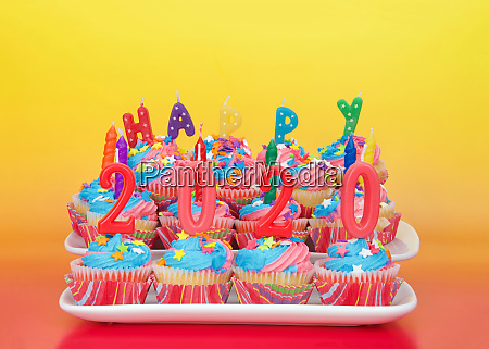 white cupcakes with rainbow colored frosting