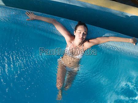 woman enjoying bath in swimming pool