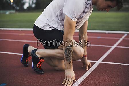 runner on tartan track in starting
