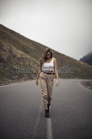 blonde woman walking on a road