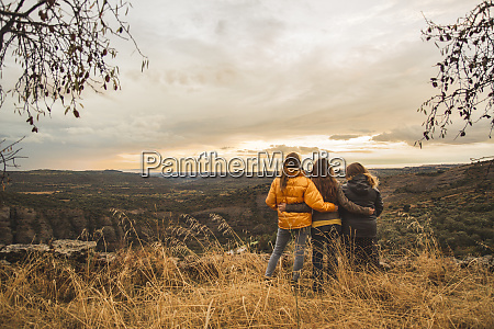 spain alquezar three friends embracing on