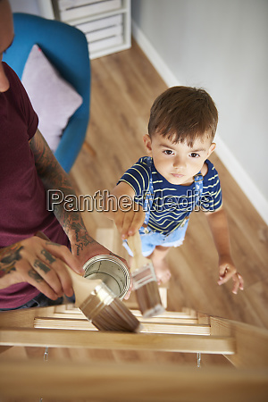 father and son painting a ladder