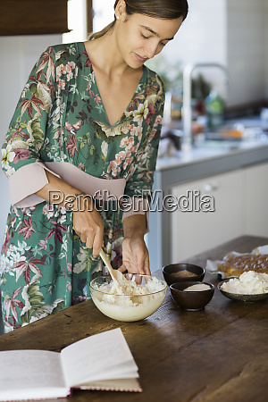 young woman preparing cake dough