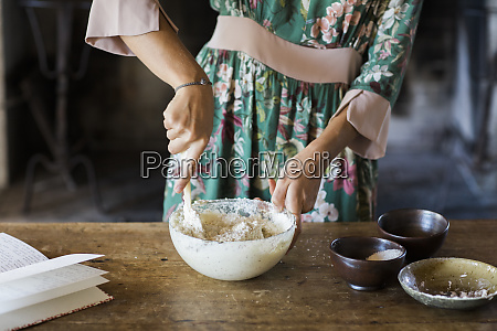 young woman preparing cake dough partial