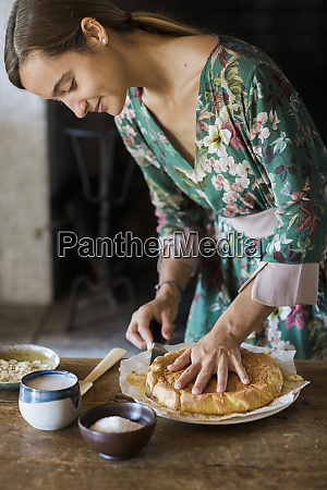 young woman cutting home baked cake