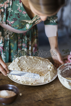 young woman preparing home baked cake