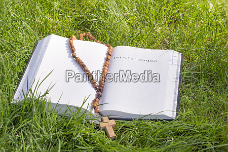 bible with rosary on green grass