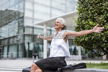 happy senior woman with baggage sitting