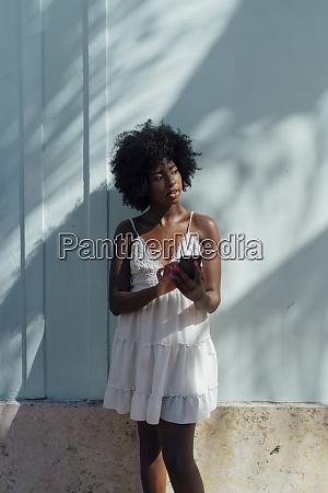 young woman wearing white dress using