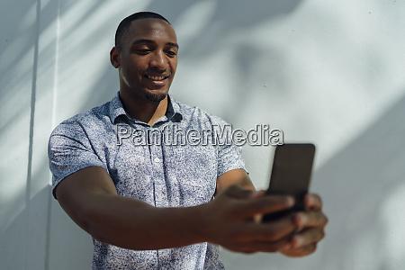 smiling young man wearing shirt taking