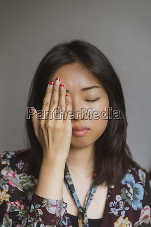 portrait of woman covering eye with