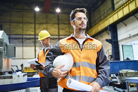 two men wearing protective workwear looking