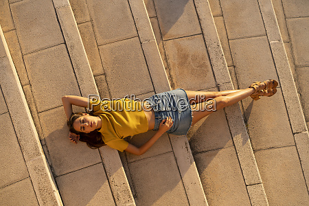 young woman lying on steps outdoors