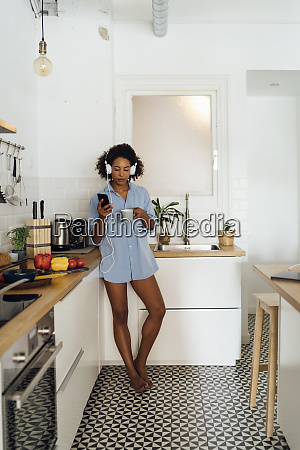 woman with headphones using smartphone and