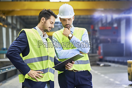 two managers wearing protective workwear looking
