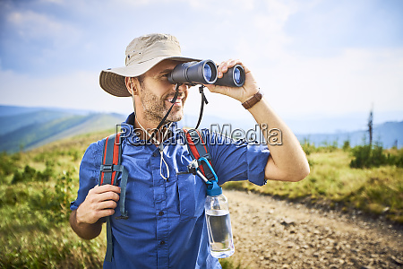 man looking through binoculars during hiking