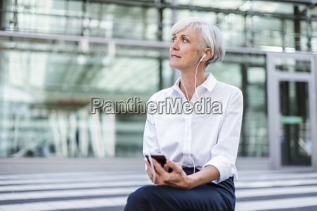 senior businesswoman sitting outside with smartphone