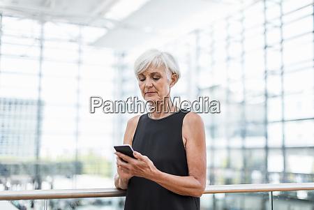 senior woman standing at railing using
