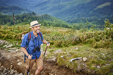 smiling man hiking in the mountains