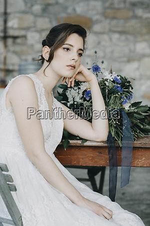pensive young woman wearing wedding dress