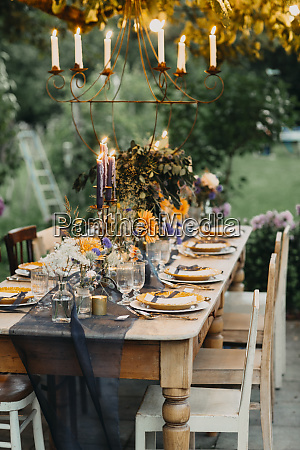 festive laid table with candles outdoors