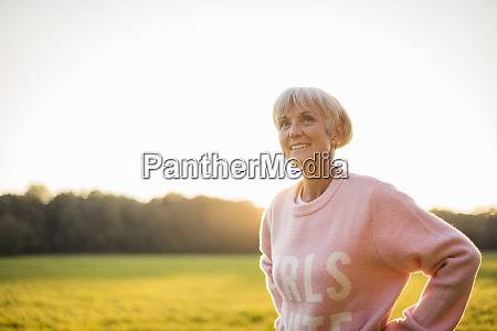 smiling senior woman standing on rural