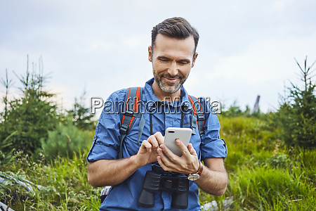 smiling man checking his cell phone