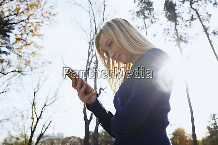 smiling blond woman using smartphone in